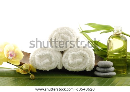Spa treatment- bowl of towel and massage oil ,orchid, stacked stones and bamboo leaf - stock photo