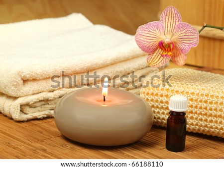 Spa treatment for beauty and relax. Candle, oil and orchid flower - stock photo