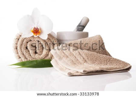 Spa treatment towel orchid pestle and mortar on reflective white surface - stock photo