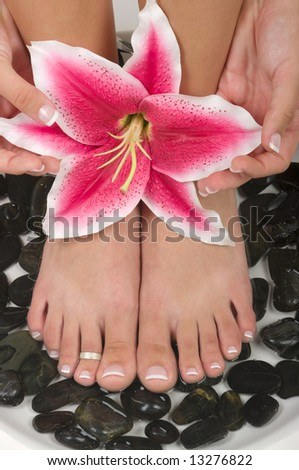 Spa treatment with beautiful lily and therapeutic stones - stock photo