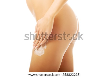 Spa undressed woman applying cream on thigh. - stock photo