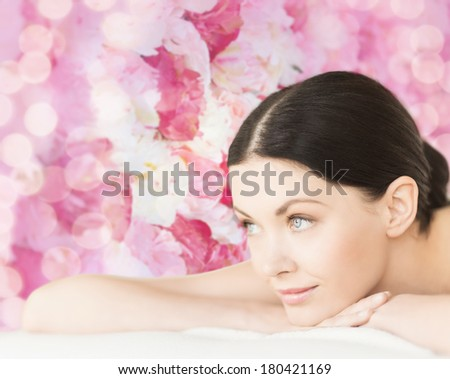spa, vacation and resort concept - smiling woman in spa salon lying on the massage desk - stock photo