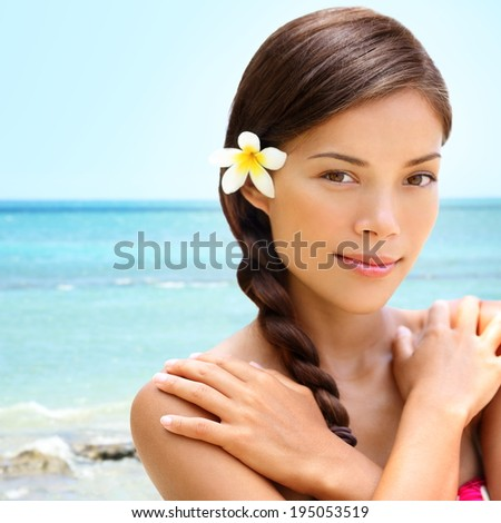 Spa wellness beach beauty woman relaxing looking at camera on Hawaii beach. Beautiful serene and peaceful young mixed race Asian Caucasian female model on holiday travel resort. Flower in braided hair