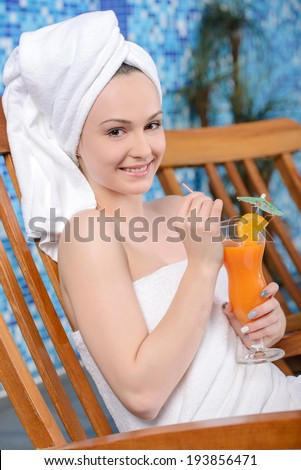 Spa & Wellness. Closeup of pretty smiling woman with juice by the pool - stock photo