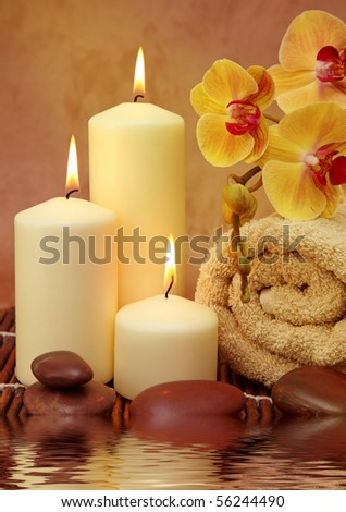 Spa with white candles on a brown backdrop - stock photo