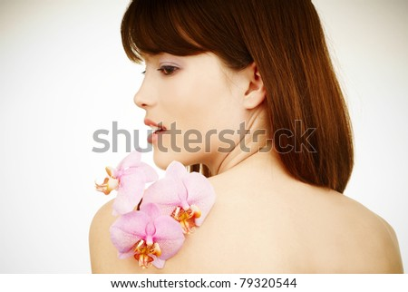 Spa woman - an orchid on beatiful woman's naked shoulders - stock photo