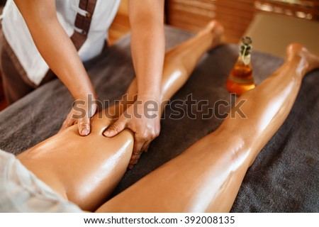 Spa Woman. Aromatherapy Oil Leg Massage Therapy. Masseur Massaging Sexy Young Long Female Legs In Cosmetology Salon. Beauty Treatment Concept. Relaxing Body Procedure. Skin Care, Wellness, Lifestyle - stock photo