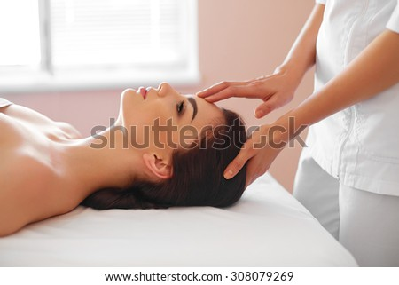 Spa Woman. Beautiful Young Woman Getting a Face Treatment at Beauty Salon. Face Massage