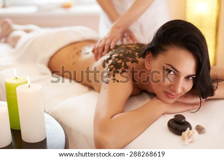 Spa Woman. Brunette Getting a Marine Algae Wrap Treatment in Spa Salon - stock photo