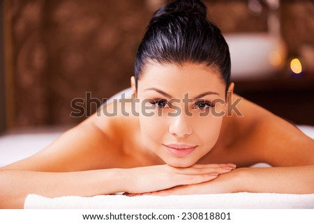 SPA woman. Front view of beautiful young shirtless woman lying on massage table and looking at camera - stock photo