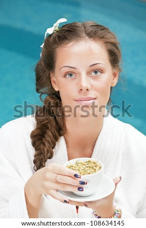 spa woman in bathrobe with cup of tea