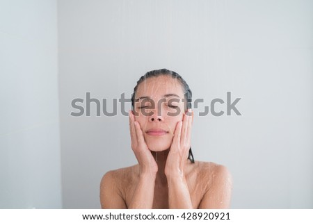 Spa woman showering relaxing under running water in hot shower. Closeup of Asian female adult face enjoying relaxation time meditating in warm bath cleaning face and body. - stock photo