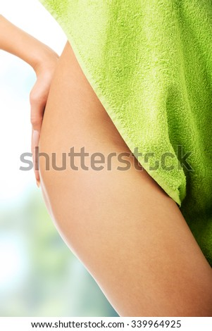 Spa woman wrapped in towel showing her thigh - stock photo