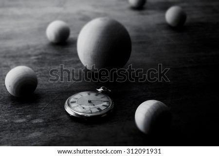 Space and time representation.  Wooden spheres on a grungy old desk, with an pocket watch. Focus on watch. Shallow depth of field. - stock photo