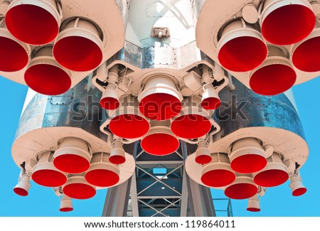 Space rocket engine on blue sky background - stock photo
