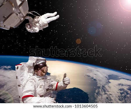 Space scene, astronauts against earth. The elements of this image furnished by NASA.