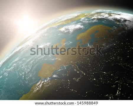 Space view of the sun rising over Europe on planet Earth. Elements of this image furnished by NASA. - stock photo