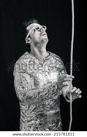 Spaceman touching rope and looking up. - stock photo