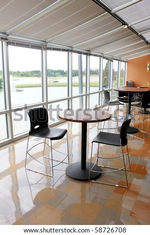 Spacious area with tables and chairs - stock photo