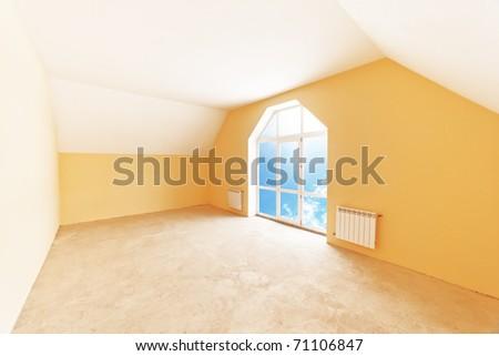 Spacious attic room interior, sky view in window. - stock photo