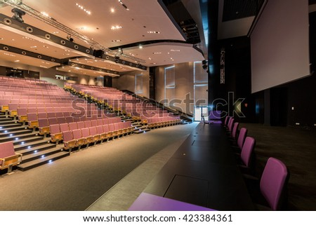 Spacious auditorium with rows of wood chairs and large performance platform with long, black table and purple chairs - stock photo