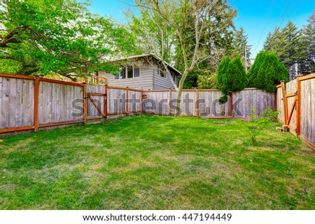 Spacious backyard area with brown wooden fence and green lawn - stock photo
