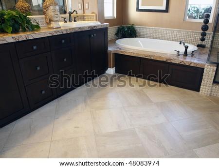 Spacious bathroom floor with a modern tub. - stock photo