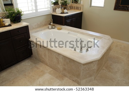 Spacious bathroom with a modern tub and tile floor. - stock photo