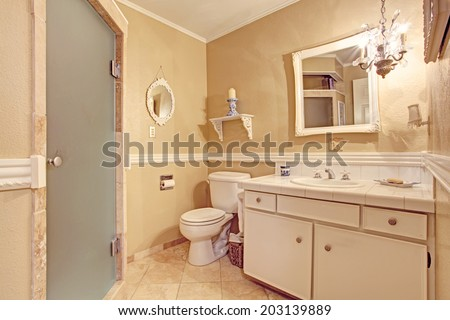 Spacious bedroom in old house with walkout deck. View of  bed in white and blue colors, floral antique chair and cabinets - stock photo