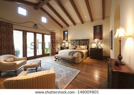 Spacious bedroom with beamed wooden ceiling - stock photo