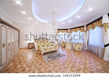 Spacious bedroom with gilt double bed and bedside tables in classic style. - stock photo