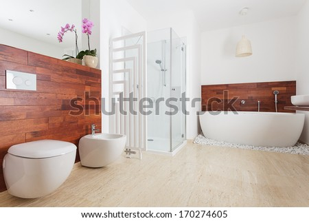 Spacious bright bathroom with shower and bath - stock photo