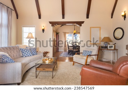 Spacious bright Craftsman home interior with beautiful inlaid hardwood floors, high ceilings with dramatic corbel beams, arched niches, white handwoven rug dining room area with bookshelves.  - stock photo