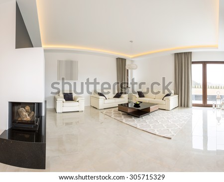 Spacious bright living room with fireplace and marble floor - stock photo
