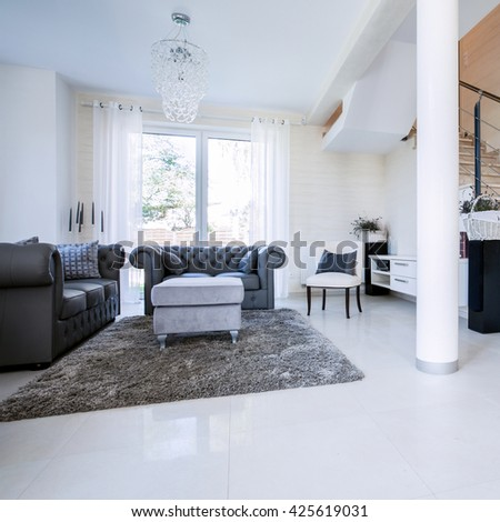 Spacious, bright sitting room with stone staircase - stock photo