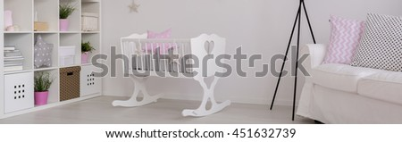 Spacious child room in white with cradle, shelving unit and sofa - stock photo