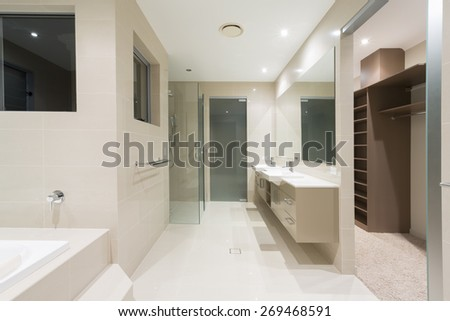 Spacious contemporary bathroom with spa and walk in robe - stock photo