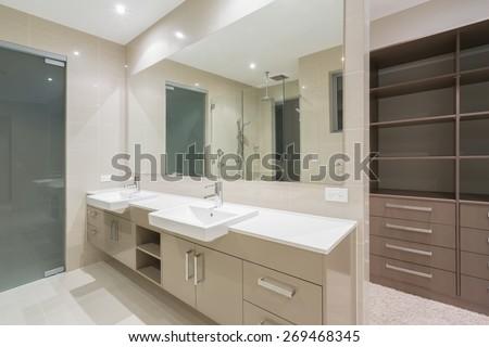 Spacious contemporary bathroom with walk in wardrobe - stock photo