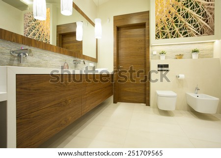 Spacious contemporary washroom with long wooden basin - stock photo