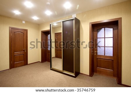 Spacious corridor with a case-compartment and three doors - stock photo