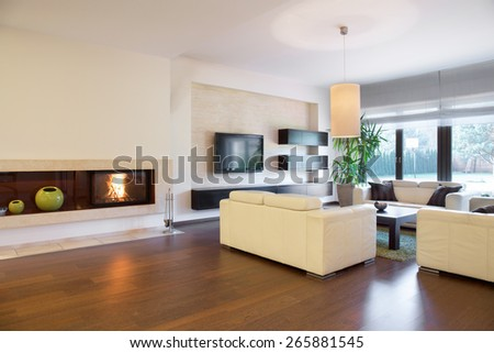 Spacious cozy living room with lighted fireplace - stock photo