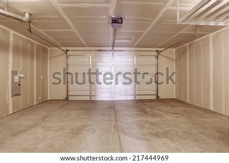 Spacious empty garage interior with concrete floor - stock photo
