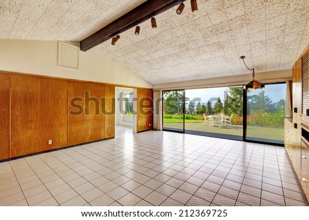 Spacious empty living room overlooking beautiful view of Puget Sound. High vaulted ceiling and wood trim. Build in 1952. Unique old modern home. - stock photo