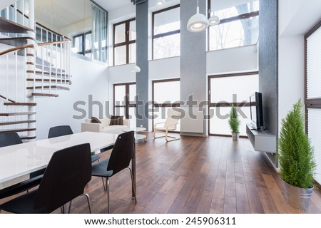 Spacious family room with wooden parquet and big windows - stock photo