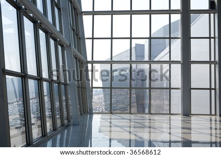 Spacious glass room in modern building of grey color