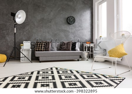 Spacious, grey living room with sofa, chair, modern standing lamp, small wood table and decorative carpet - stock photo
