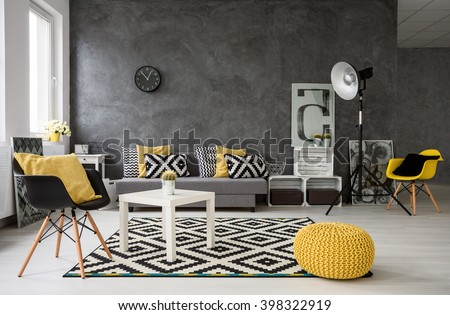 Spacious, grey living room with sofa, chairs, standing lamp, small coffee-table, decorations in yellow, black and white  - stock photo