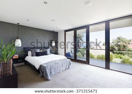 Spacious interior of designer master bedroom in luxury contemporary Australian home - stock photo