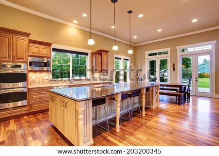 Spacious kitchen interior with kitchen island and dining area in luxury house