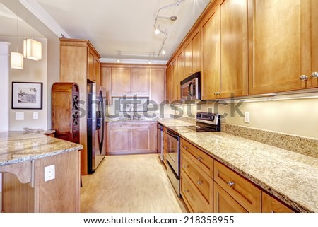 Spacious kitchen room with wooden storage cabinets, granite tops, steel appliances and island